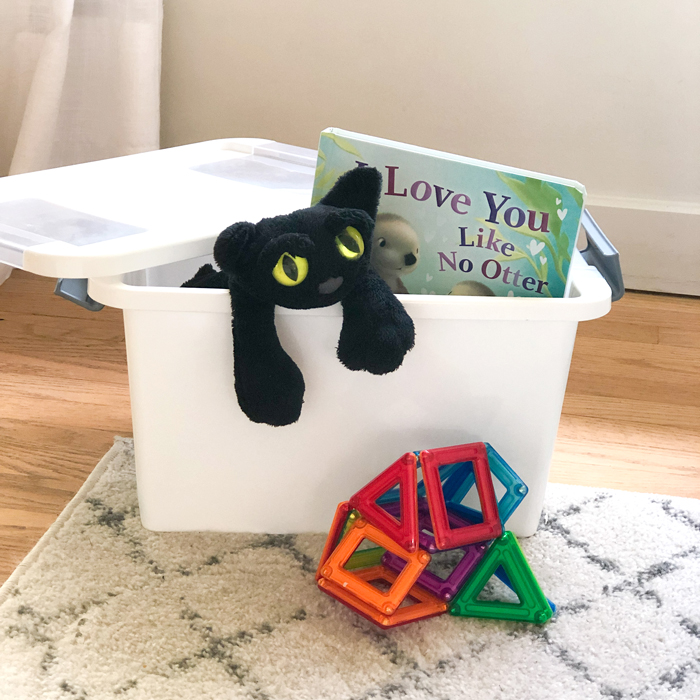 quiet activity box filled with stuffed animal, book and toys for occupying a toddler when you have a newborn