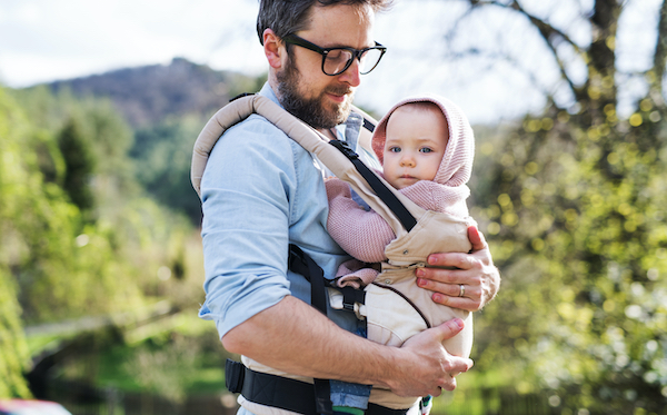 A father wears his daughter while out and about