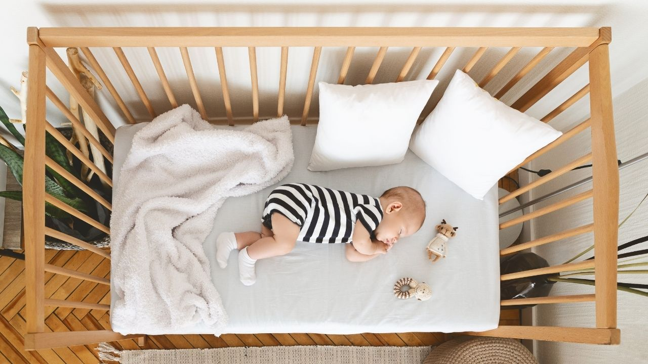 baby lying in crib with a blanket, two pillows and two toys