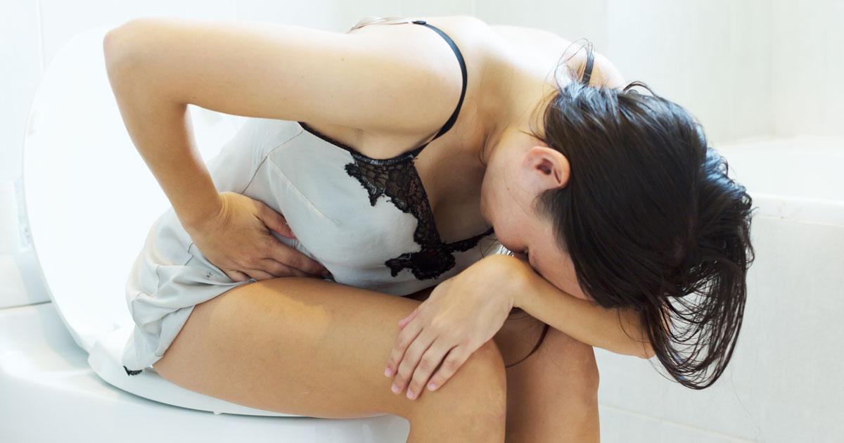 Woman sitting on the toilet having pain in her stomach. Constipation.